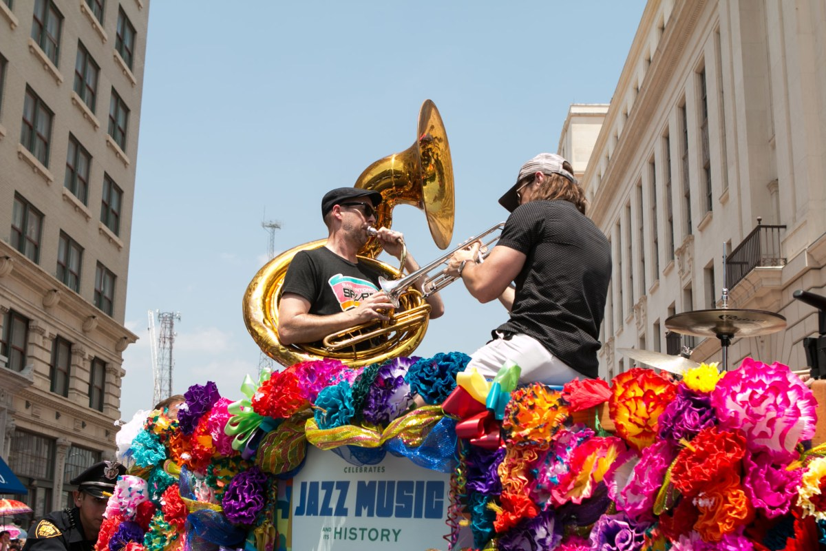 Jazz Musicians ride on top of a vintage car during the Battle of Flowers Parade.