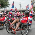 A large group bikes through the Battle of Flowers Parade.