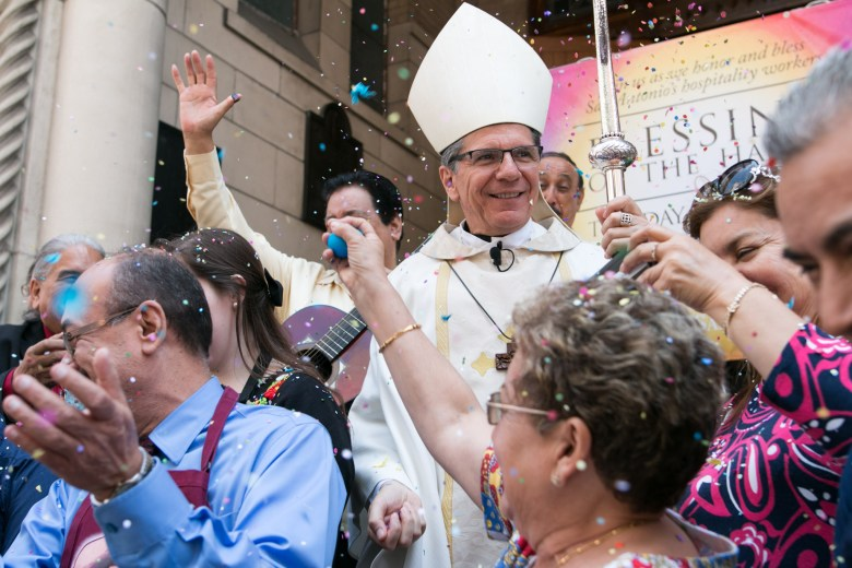 """Archbishop Gustavo García-Siller and hospitality workers throw confetti into the air after the """"Blessing of the Hands"""" at Saint Mary's Catholic Church."""