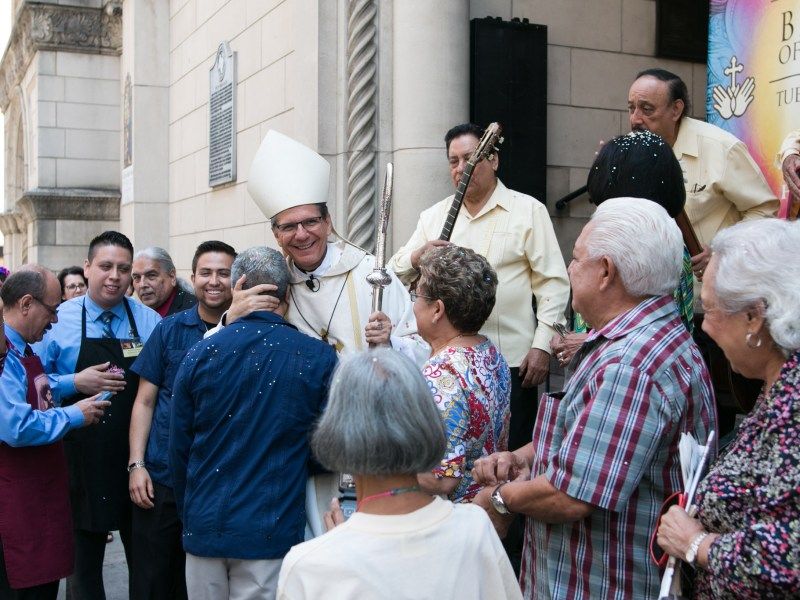 """Archbishop Gustavo García-Siller embraces Benito Espinoza after bestowing the """"Blessing of the Hands"""" at Saint Mary's Catholic Church."""