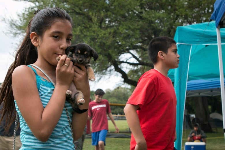 Alicia, 9, holds Pringles the puppy during Easter weekend at Brackenridge Park.