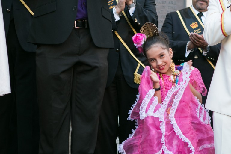 A girl peeks through the crowd at the crowning of El 69th Rey Feo.