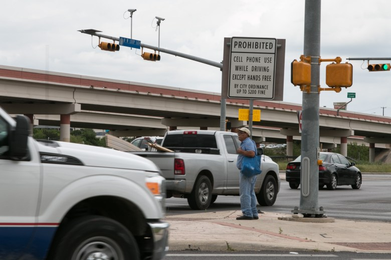 "A man waits for the ""walk"" signal at the corner of W Loop 1604 N and Culebra Road."