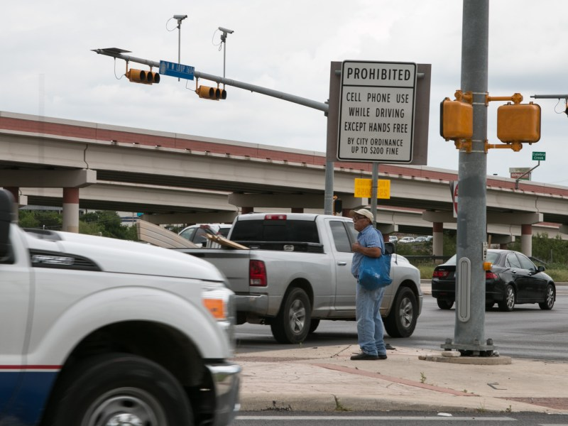 "A man waits for the ""walk"" signal at the corner of W Loop 1604 N and Culebra Road."