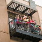 A group of women watch the Fiesta Flambeau Parade from their balcony.