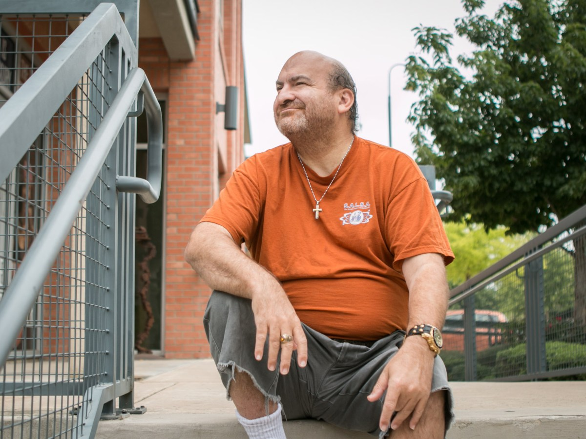 James Meadours sits outside of his apartment complex on the steps where he typically waits for public transportation to arrive.