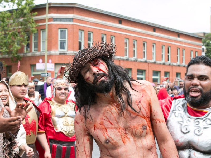 An actor portraying Jesus stumbles in pain at the Passion of Christ Procession.