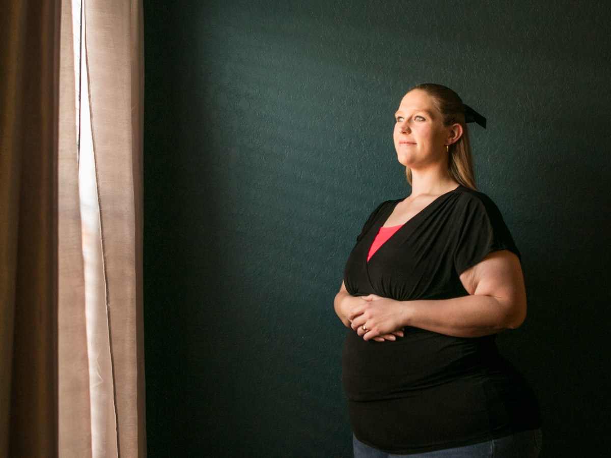 Sarah Estrada stands in her home with her hands on her pregnant belly.