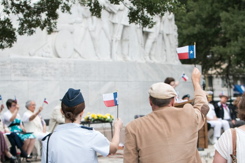 The crowd raises Texas flags during the San Jacinto Victory Celebration in Alamo Plaza.