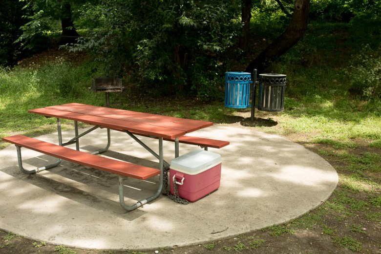 A cooler is chained to the side of a picnic table at Brackenridge Park marking to others that this is a claimed camping spot.