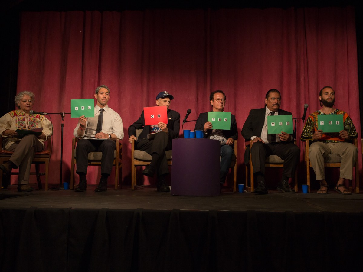 """Mayoral candidates hold up cards stating """"yes"""" or """"no"""" regarding their stances on a specific issue."""