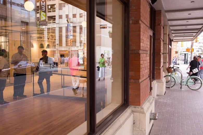 Pedestrians pass on Houston Street and Navarro Street alongside the Vogue Building.