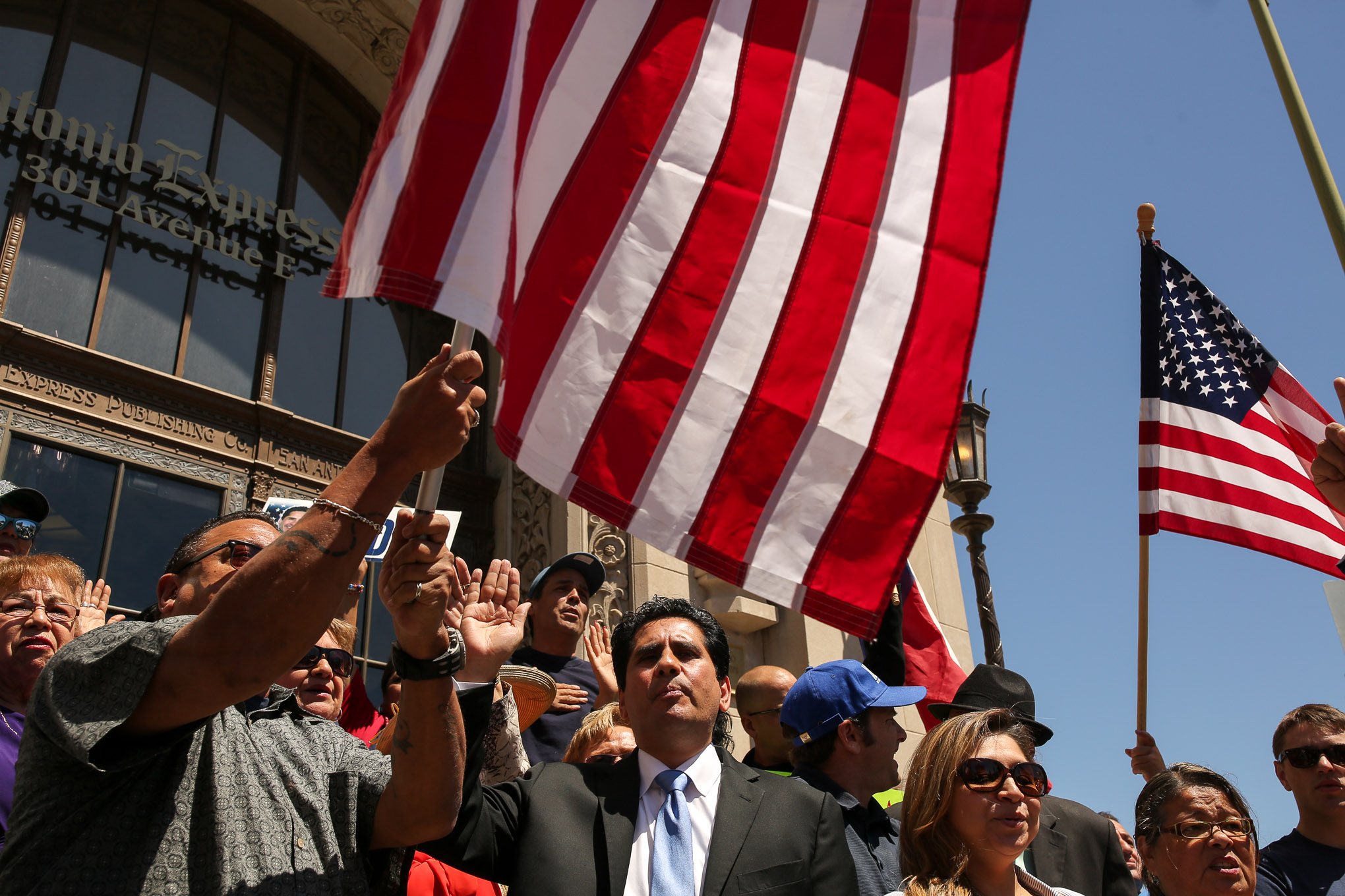 Manuel Medina along with his supporters recite the United States Pledge of Allegiance on the steps of the San Antonio Express News.