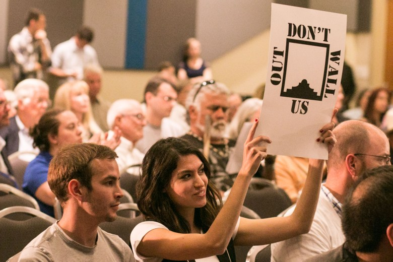 Italia Aguilera (right) holds up a sign at the public input meeting for the Alamo Master Plan.