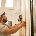 Artist Camilo Villalvilla mounts a work onto the wall before the Cuerpo Cubano / Cuban Body show at Bihl Haus Arts.