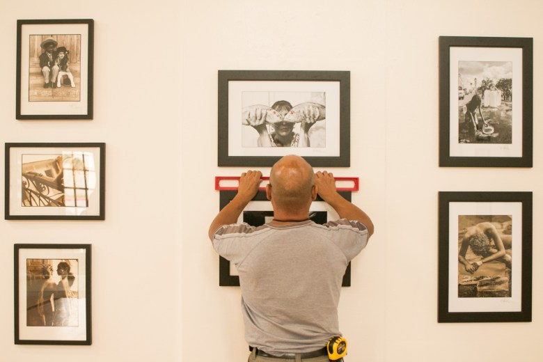 Bihl Haus Arts installer Estevan Arredondo confirms that the photographs by Omar Valenti are hung straight for the Cuerpo Cubano / Cuban Body show.
