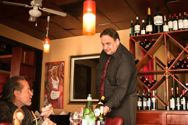 Bistro Vatel server Pascal Vincent presents wine to longtime patron Jerry Gore, a frequent lunch diner.