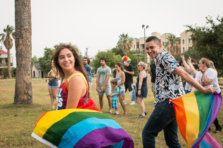 (From left) Jennifer Jaster and Jorge Estevez walk in front of the crowd with rainbow flags at the Gay Pride Mob Flash Dance in front of Mayor Ivy Taylors house.