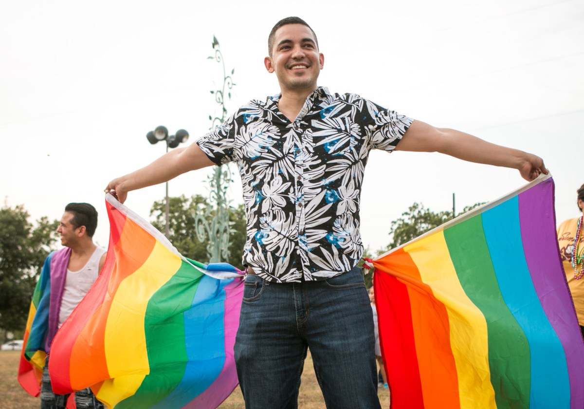 Jorge Estevez waves two rainbow flags at the Gay Pride Mob Flash Dance in front of Mayor Ivy Taylors house.