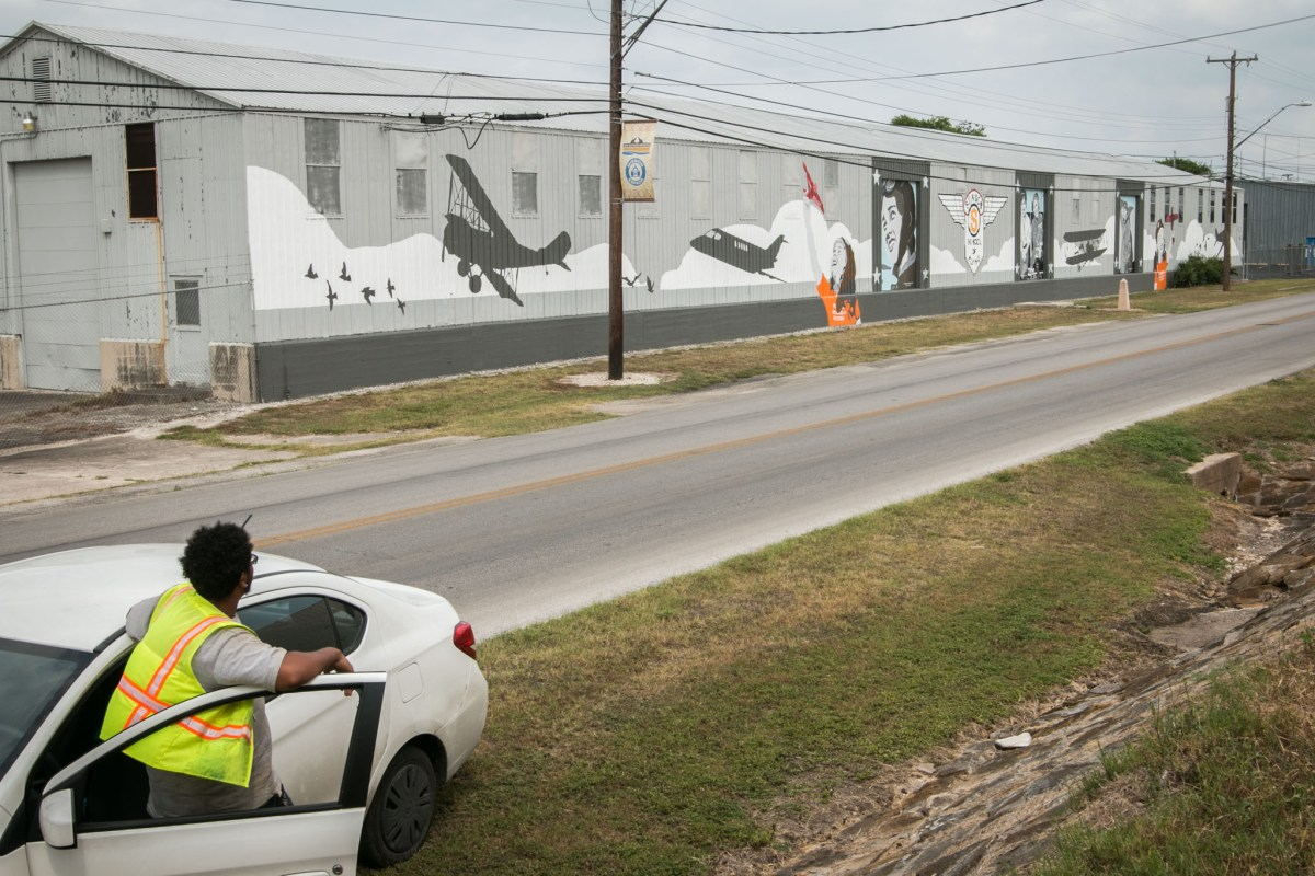 A man steps out of his car to view the mural at Stinson Municipal Airport.