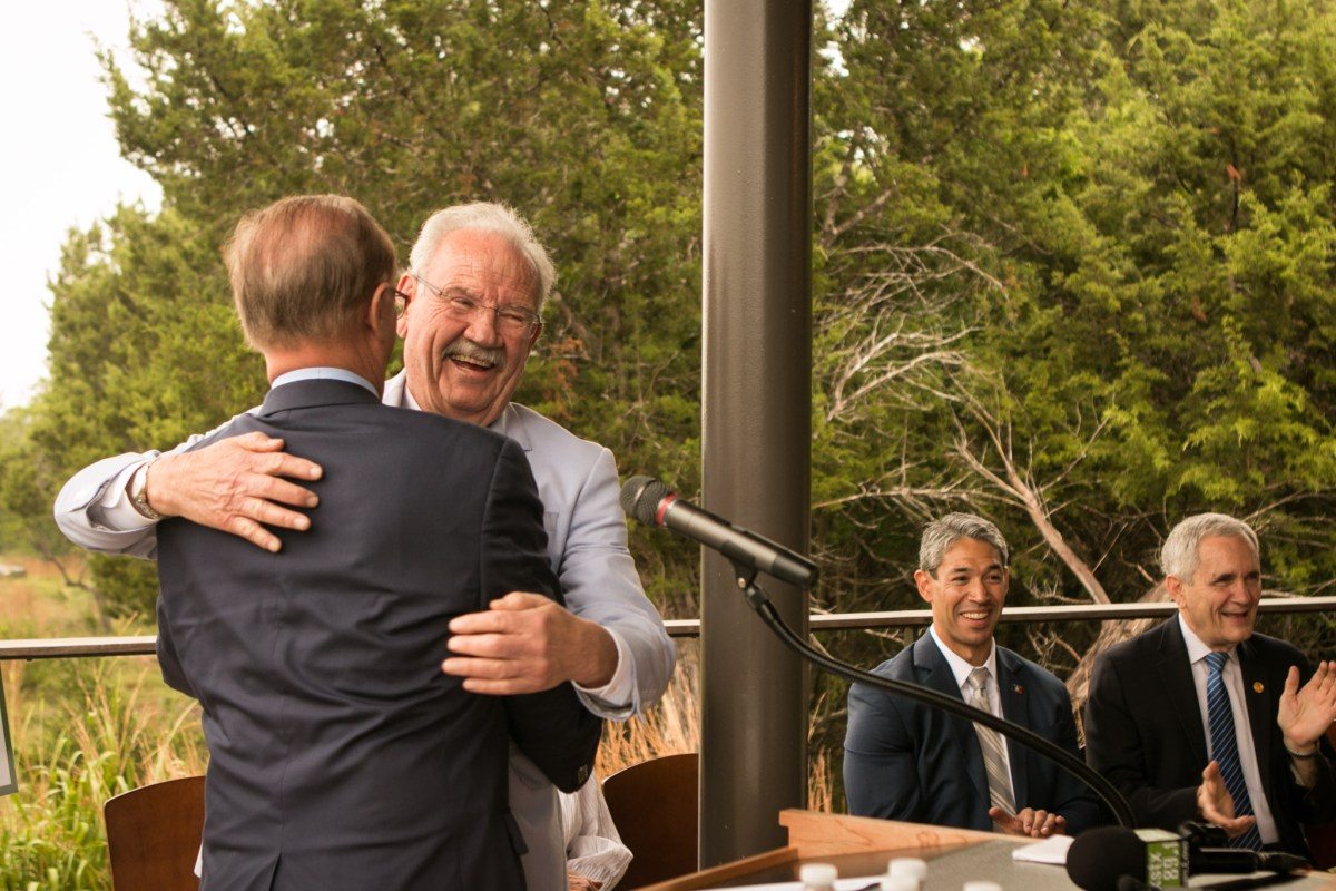 Bexar County Judge Nelson Wolff (left) hugs Phil Hardberger at the Urban Ecology Center at Phil Hardberger Park.