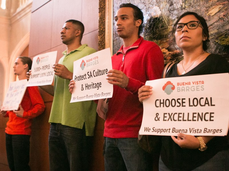 Supporters of Buena Vista Barges stand at the back of City Council chambers with signs of support for the local company.