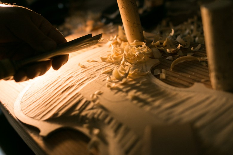 A piece of wood is shaped into a violin in Scott Albert's workshop.
