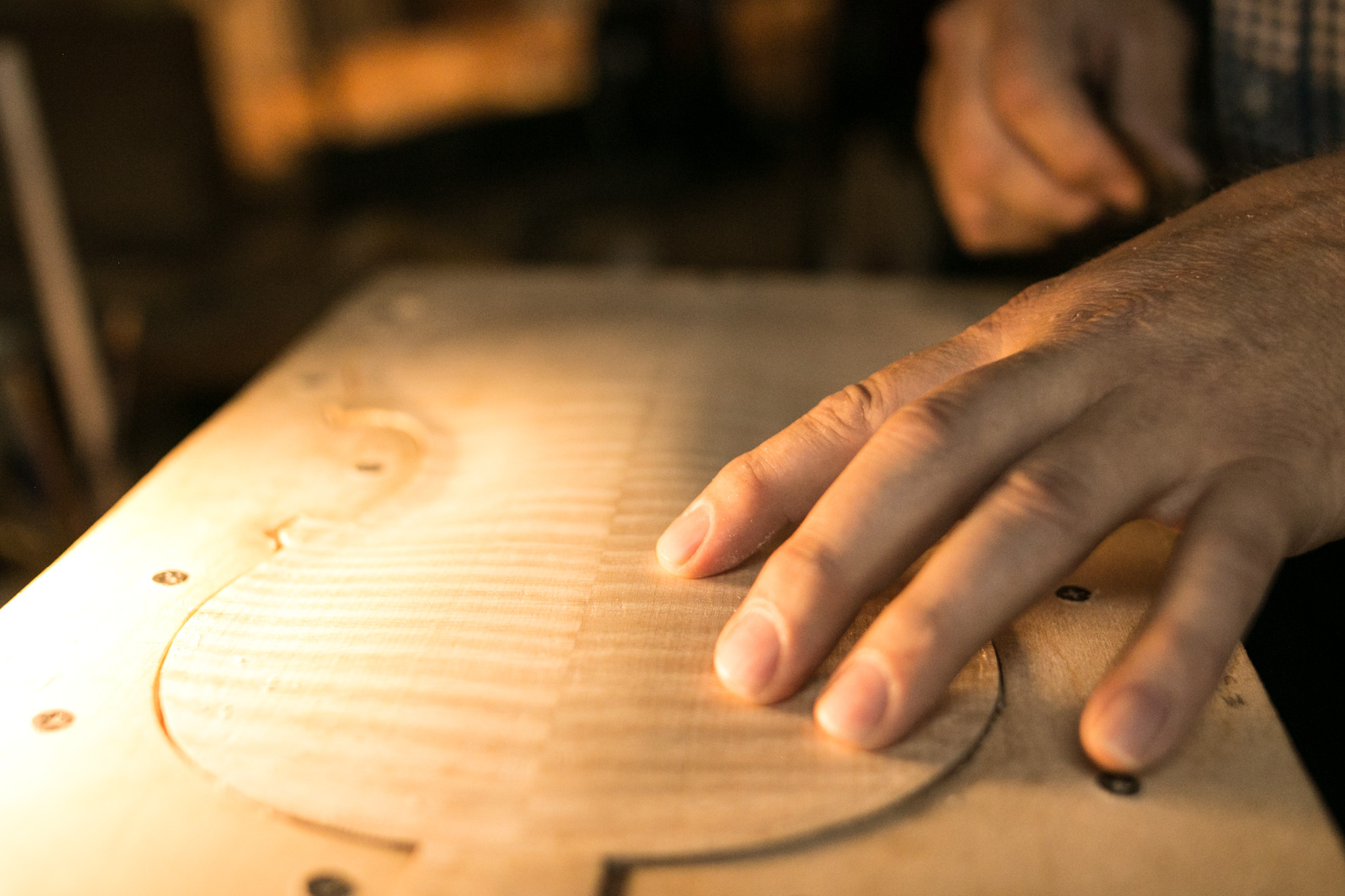 Scott Albert runs his finger over the wood to test for marks to smooth down on the violin.
