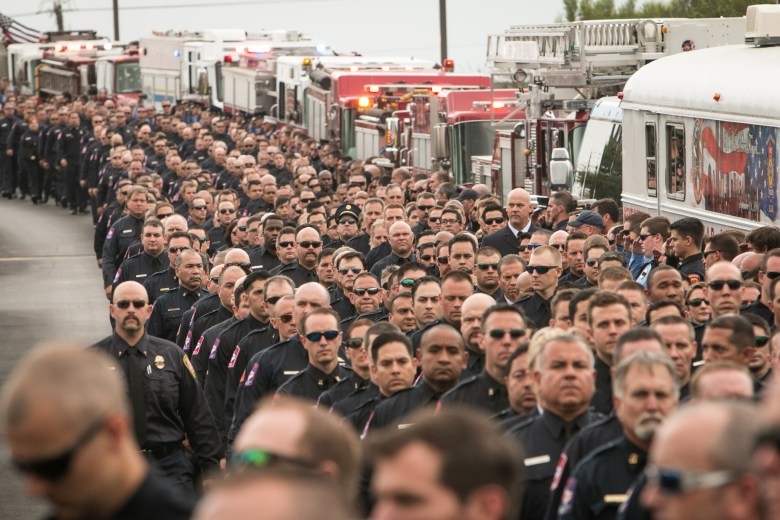 Hundreds of firefighters walk in a procession before the funeral of firefighter Scott Deem.