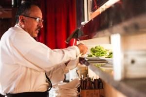 Server Ray Martinez preps a dish at Chez Vatel Bistro.