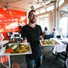 "Server Joel ""Turtle"" Cruz shows off some dishes at Bite Restaurant."