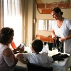 (Right) Chef Lisa Watel prepares for the kitchen while chatting with family members Sandy Theodosion (left) and Enzo Watel.