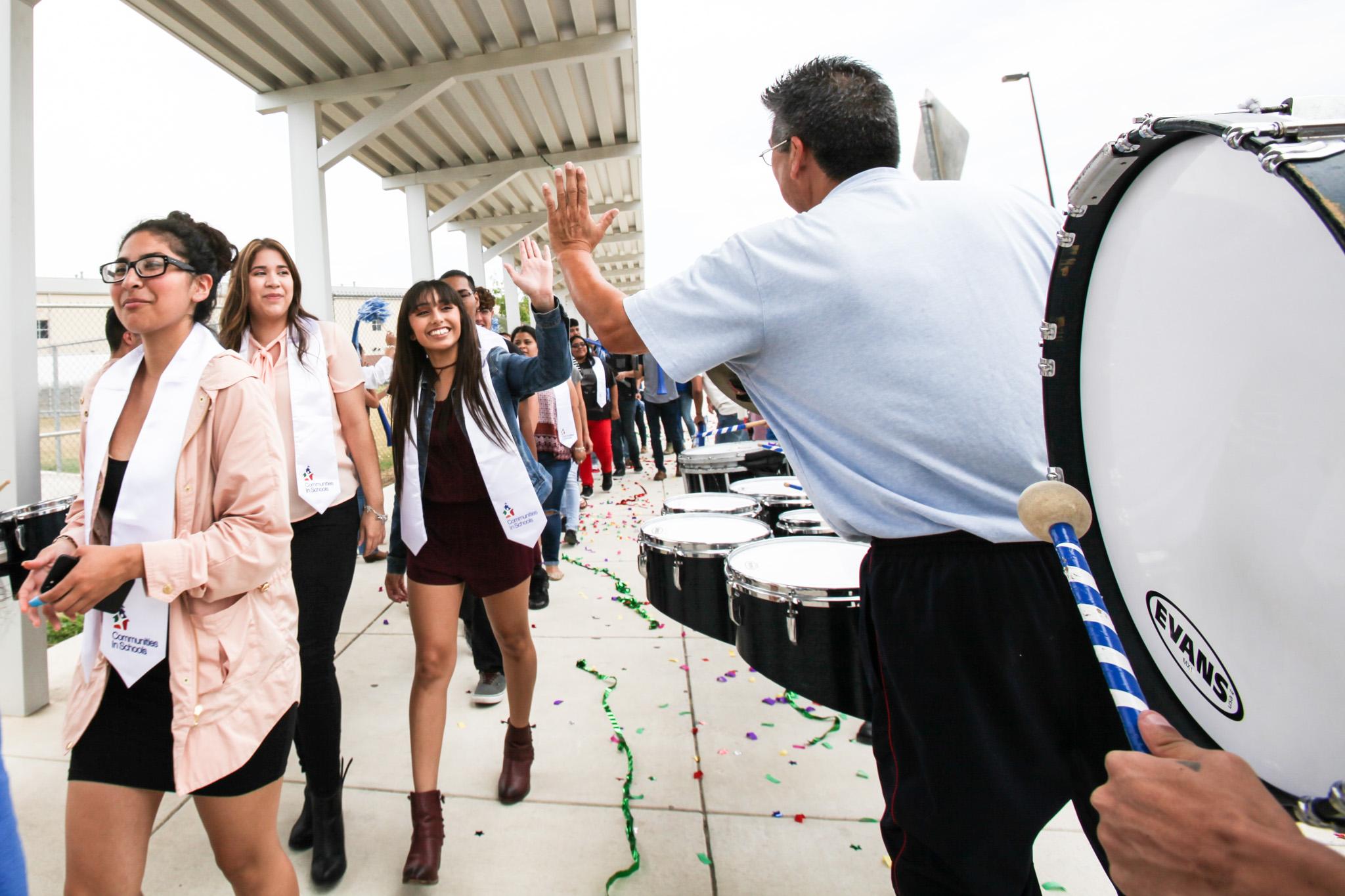 South San Antonio High School senior, Samantha Magna, high-fives the drum line at the Surprise Graduation Celebration.