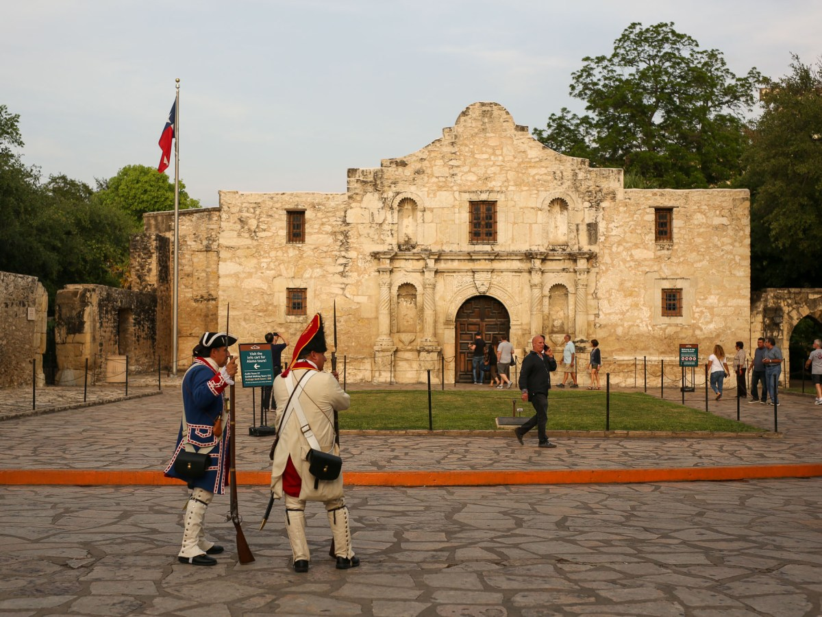 Two battle re-enactors look on as visitors wander through Alamo Plaza.