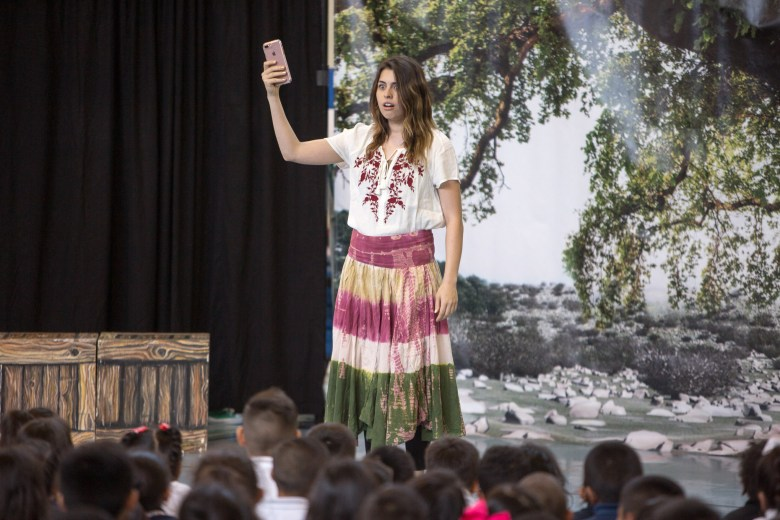 A performer holds up her phone during the performance of the opera speaking out against cyberbullying titled 'Beautiful Dreamer'.