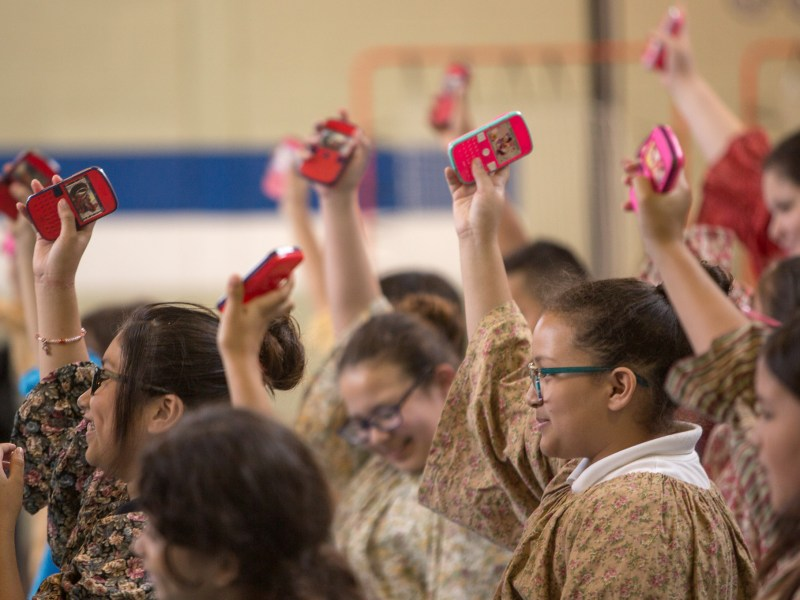 Students of Beacon Hill Elementary hold up prop cell phones during their performance.