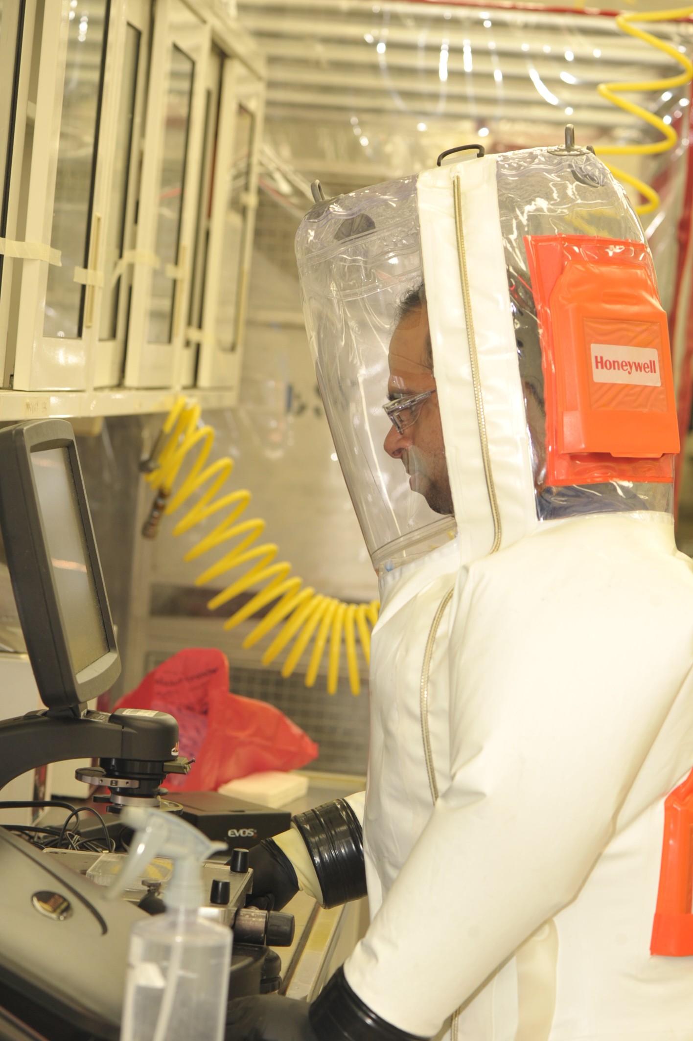 A scientist works on an experiment while wearing a protective suit inside the BSL-4 lab