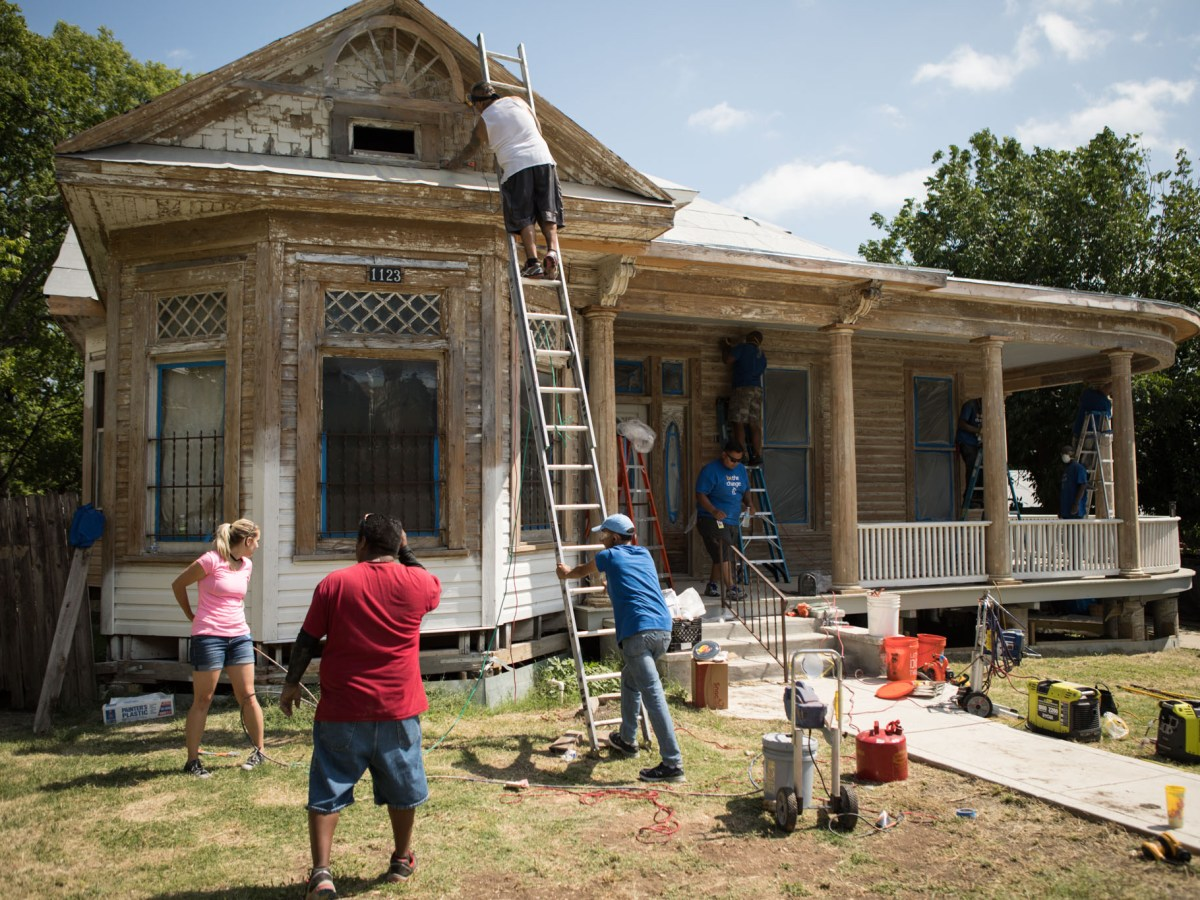 Haven for Hope Ambassadors paint the exterior of the home of Miguel Calzada.