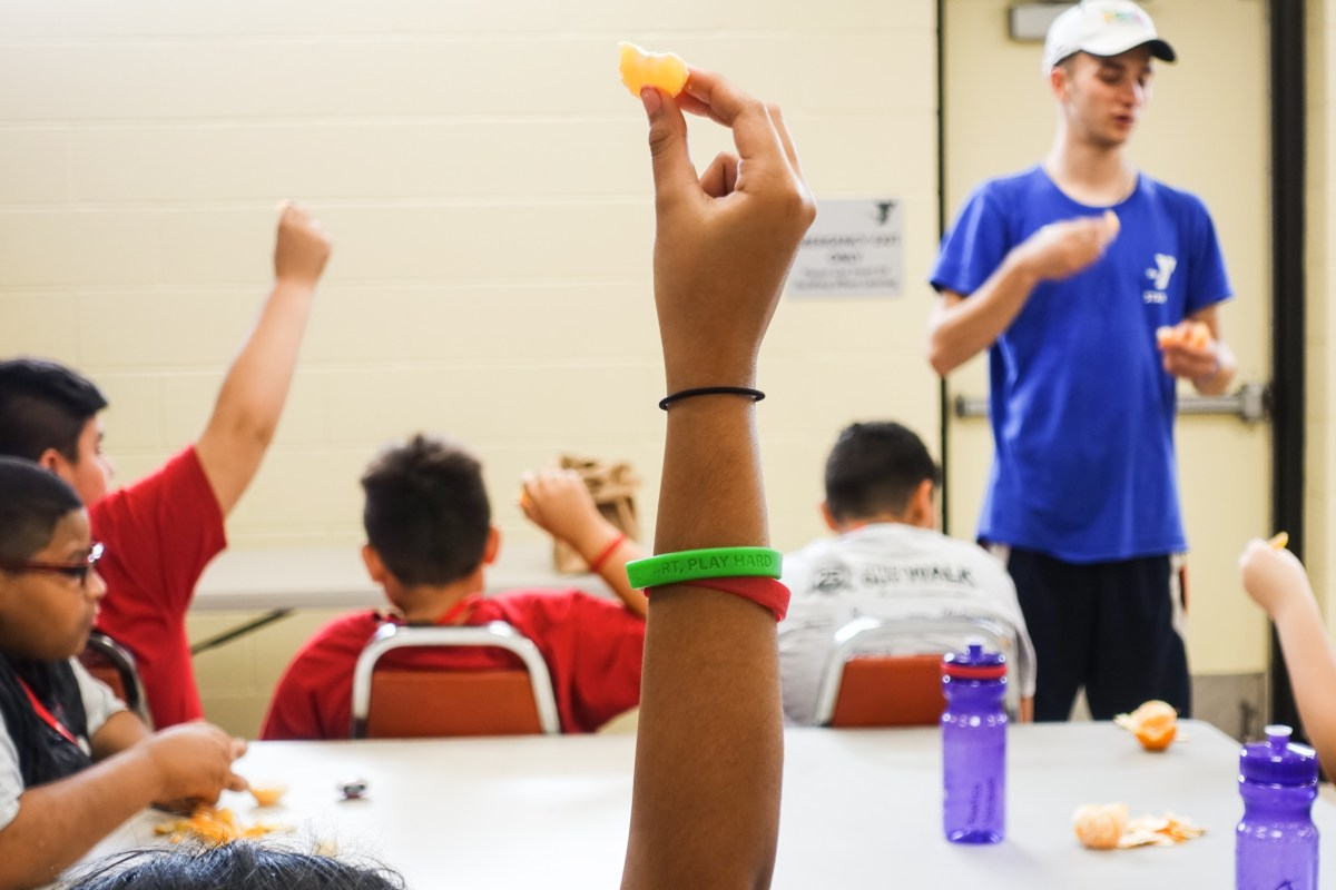 Campers hold up peeled oranges in the air during a nutrition education mindful eating class at American Diabetes Association camp.