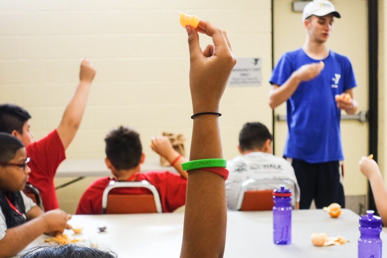 Campers hold up peeled tangerines during a session on mindful eating at Camp PowerUp.