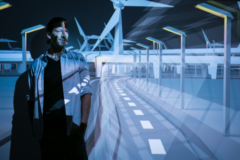 Artist Lieven van Velthoven stands in the light of his installation Headrush in the DigiPlayspace.