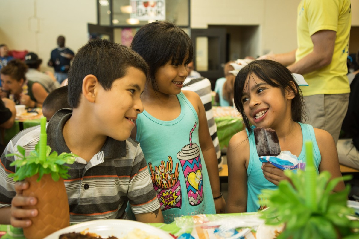 (From left) Jesus, 11, Adrianna, 6, and Angelica, 9, enjoy a meal and dessert at the Haven for Hope BBQ Bash.