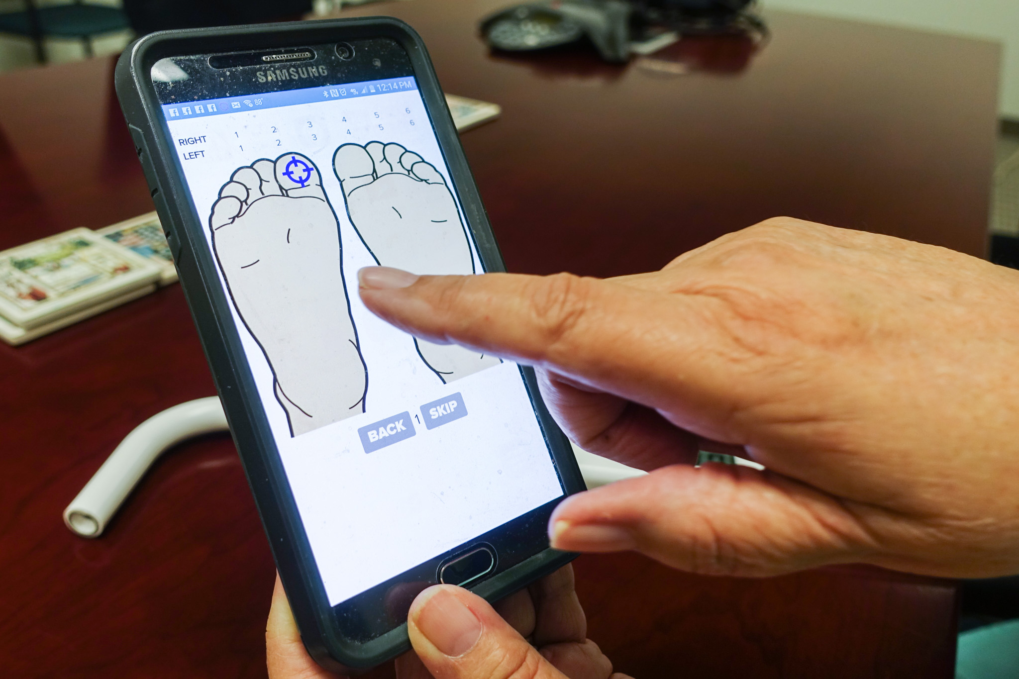 Roslyn McClendon demonstrates how to use the app for MR3 Health's diabetic foot sensor.