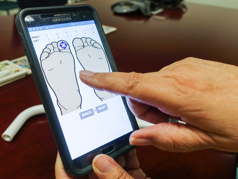 Roslyn McClendon demonstrates how to use the app for MR3 Health's diabetic foot sensor.