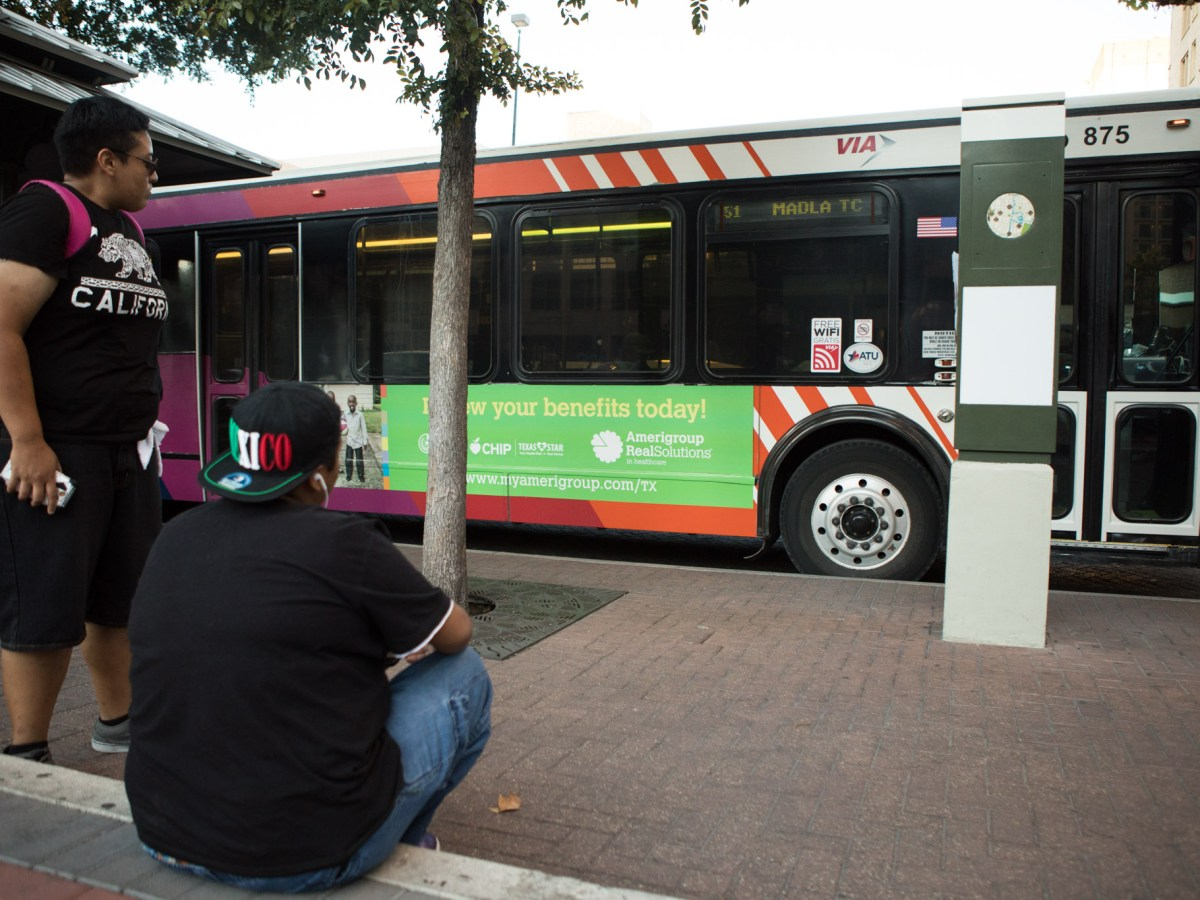 Commuters wait at the VIA Metropolitan Transit bus stop at the corner of Travis Street and St. Mary's Street.