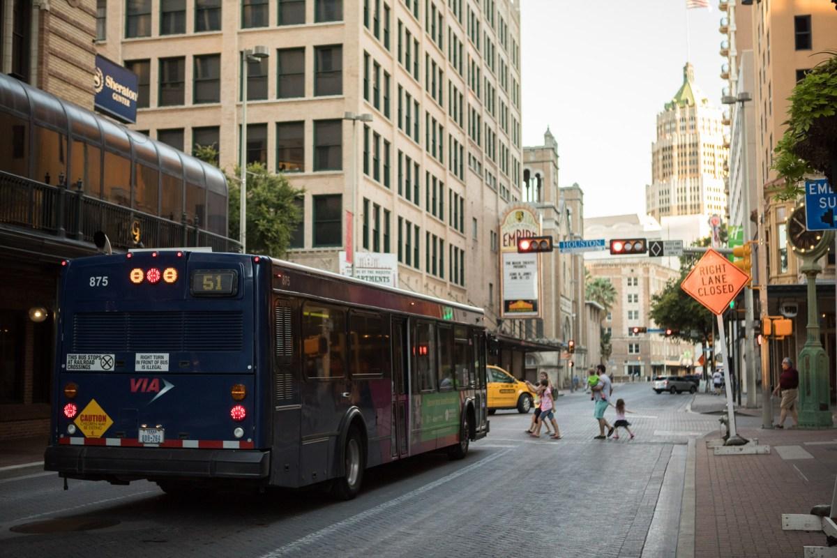 A VIA Metropolitan Transit bus stops at a red light on Houston Street.
