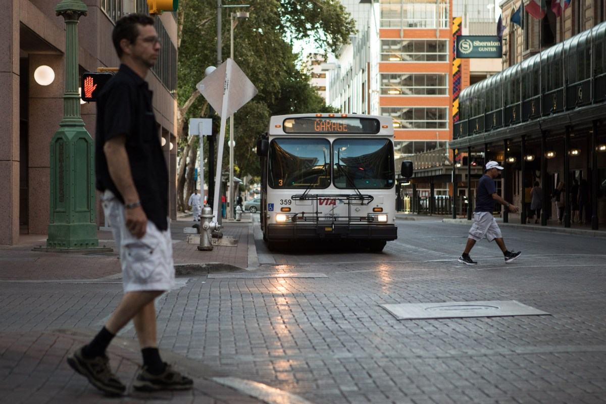 A VIA Metropolitan Transit bus stops at a red light at the corner of Houston Street and St. Mary's Street.