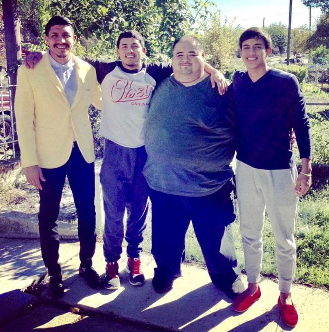(From left) Orlando Mendez-Valdez, Ajax Reyes, Abel Valdez, and Johnatan Reyes smile together in Valdez's front yard.