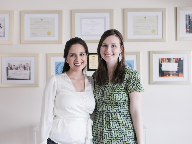 Founders of the San Antonio-based bioscience startup NovoThelium Bianca Cerqueira (left) and Lauren Cornell stand in their office in front of the many awards they have earned.
