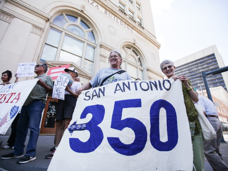 Vice president of Imagine San Antonio and former natural resources director for the Alamo Area Council of Governments Peter Bella (left) holds up a San Antonio 350 sign at the rally for the Paris climate accord.